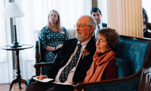David Blocher, Volunteer of the Year award recipient, and his wife listen as the Home Care and Hospice Alliance of Maine reads his nomination.