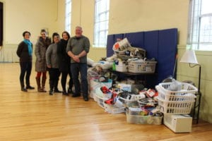 New Beginnings Staff and Androscoggin Staff stand next to the giant pile of donated items for the New Apartment kits.